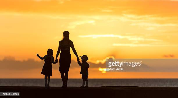 Mother and two children silhouetted in sunset