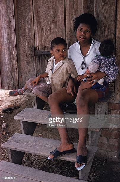 A mother and two children sit on the steps of their wooden slum home