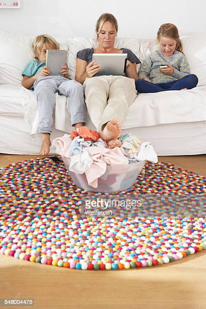Mother and two children sitting on couch using smartphone and digital tablets ignoring pile of laundry