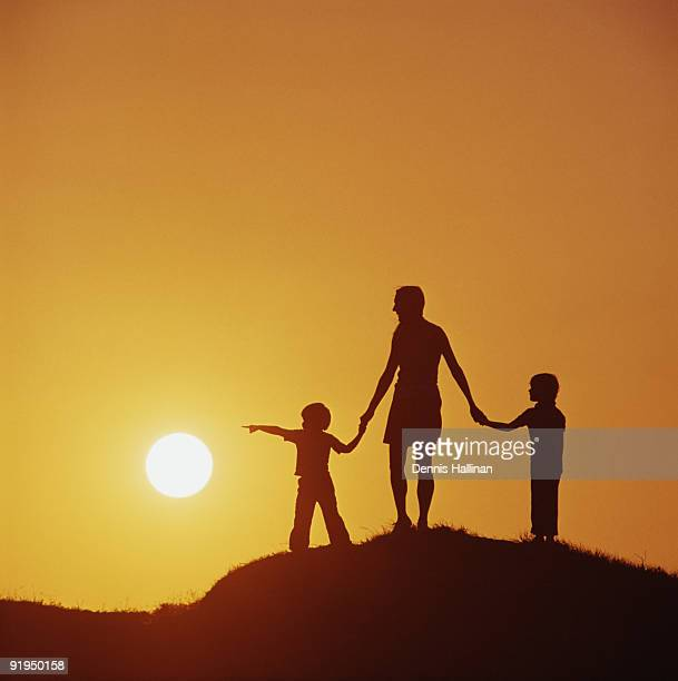 Mother and two children walking on hill at sunset
