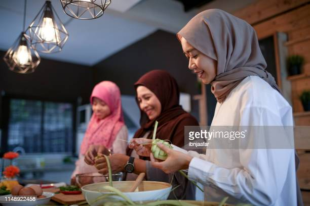 mother and two daughter preparing food - eid al adha stock pictures, royalty-free photos & images