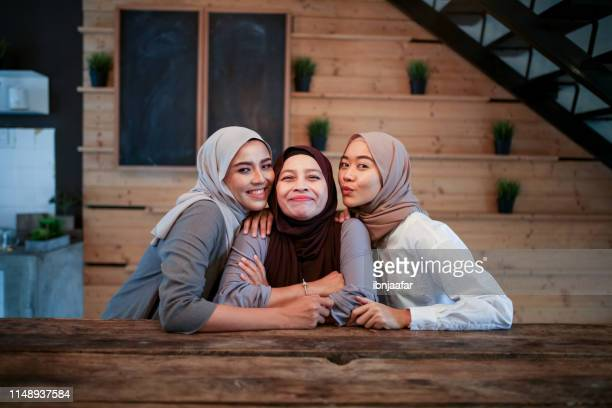 mother and two daughter smiling - eid al adha stock pictures, royalty-free photos & images