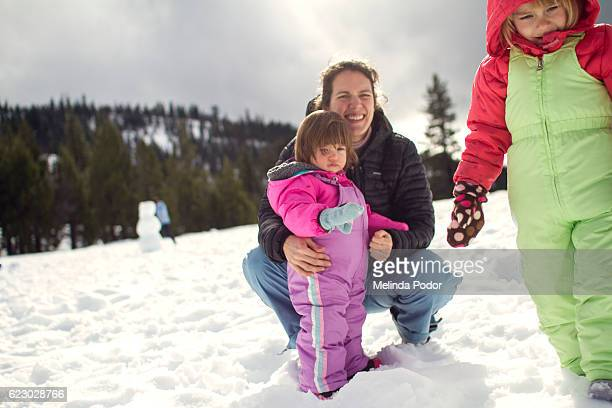 mother and two daughters enjoying snow in california, unstaged moment - out of frame stock pictures, royalty-free photos & images
