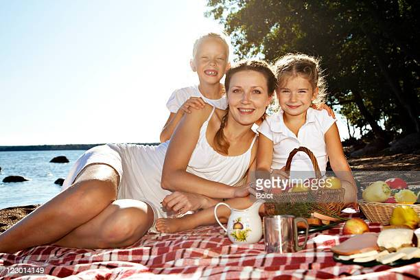 Mother and Two Daughters Having Picnic at Beach
