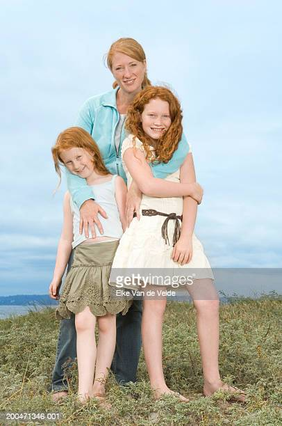 mother and two daughters (7-10) standing on beach, portrait - 10 11 years photos stock photos and pictures