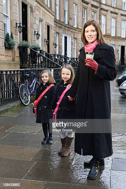 Mother and two daughters standing on pavement