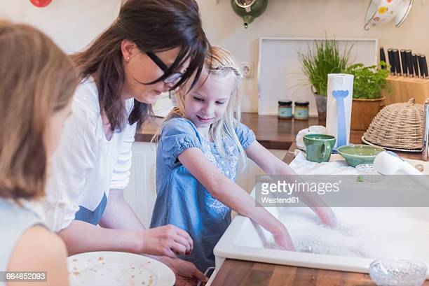 Mother and two girls washing the dishes in kitchen