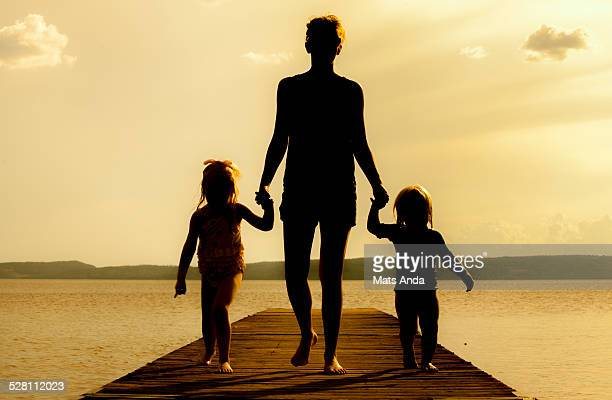 Mother and two kids on a pier in summer