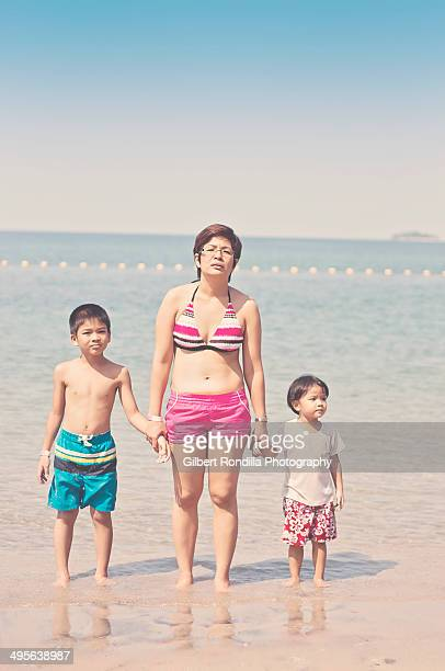 Mother and two kids on the beach, looking bored