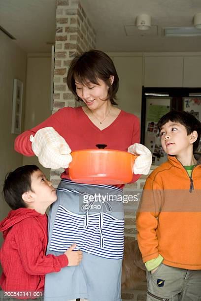 Mother and two sons (5-7) in kitchen, mother carrying hot pan