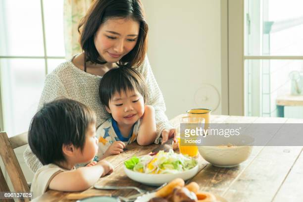 Mother and two sons looking at smart phone at table