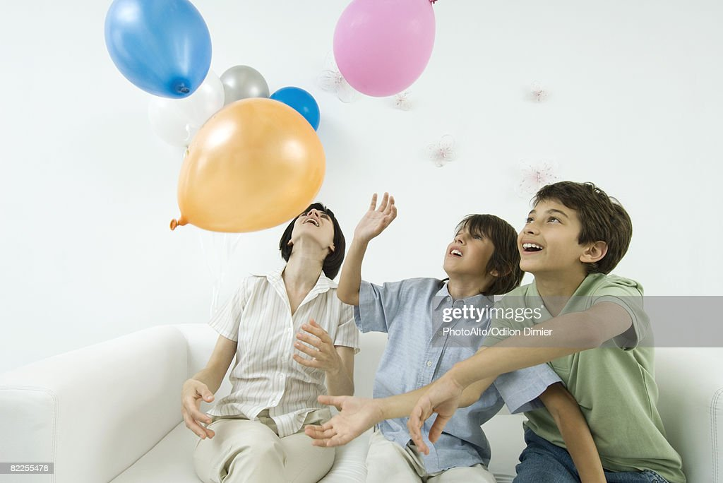 Mother and two sons playing with balloons, looking up : Stock Photo