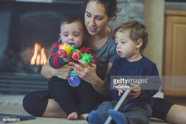 Mère et ses deux jeunes fils jouent int le salon