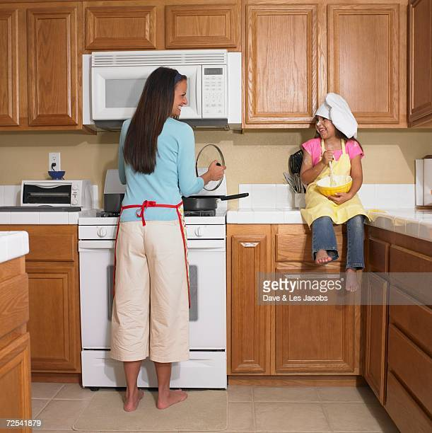 Mother and young daughter baking in kitchen