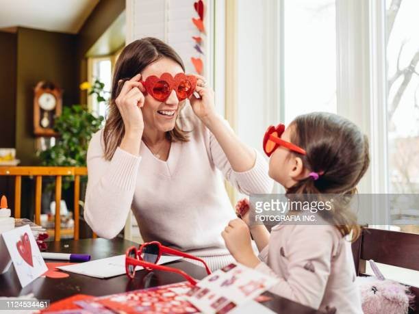 mother and young daughter crafting for valentine's day - valentine's day stock pictures, royalty-free photos & images