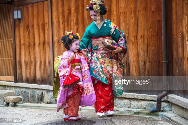Mother and young daughter dressed in traditional geisha Japanese dress. Kyoto. Japan.