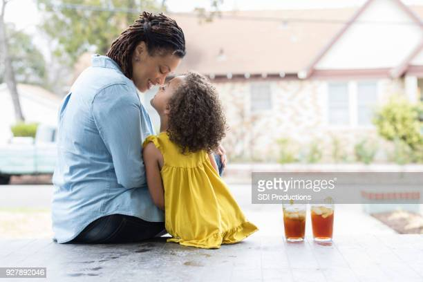 mother and young daughter enjoy sitting outside together - african american family home stock photos and pictures