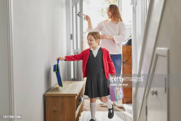mother and young daughter entering house - education stock pictures, royalty-free photos & images