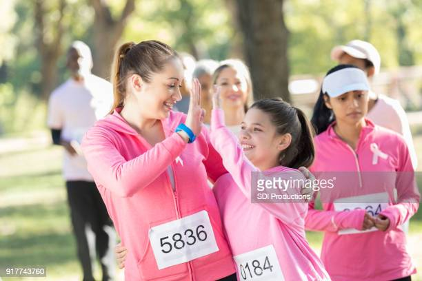 Mother and young daughter high five each other after race for cure
