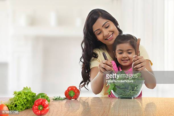 Mother and young daughter making salad for lunch in the kitchen