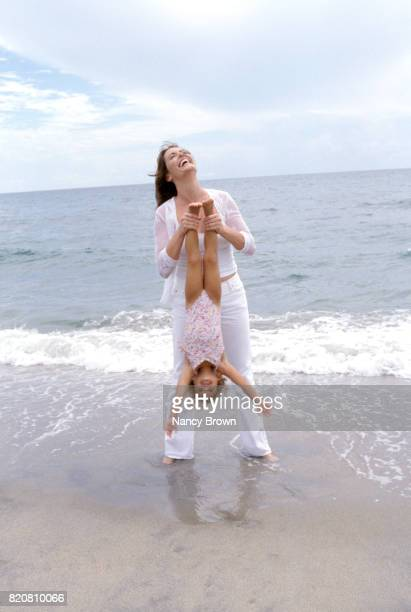 Mother and Young Daughter on Beach by Ocean Having Fun.
