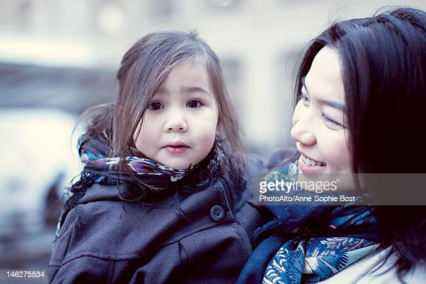 Mother and young daughter outdoors, girl looking at camera