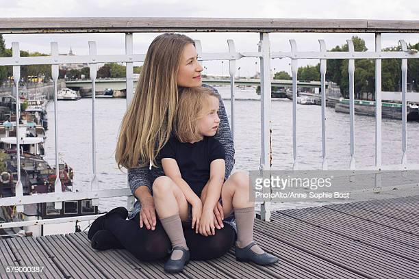 mother and young daughter sitting together on bridge over canal - anne sophie mutter stock-fotos und bilder