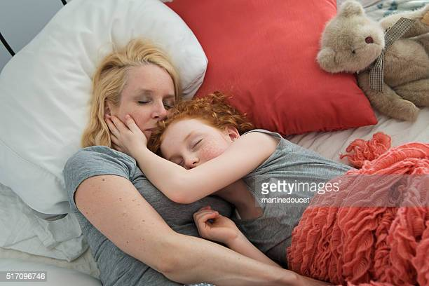 Mother and young daughter sleeping together in bedroom.