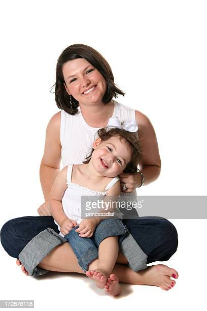 Mother and young daughter smiling and sitting on floor