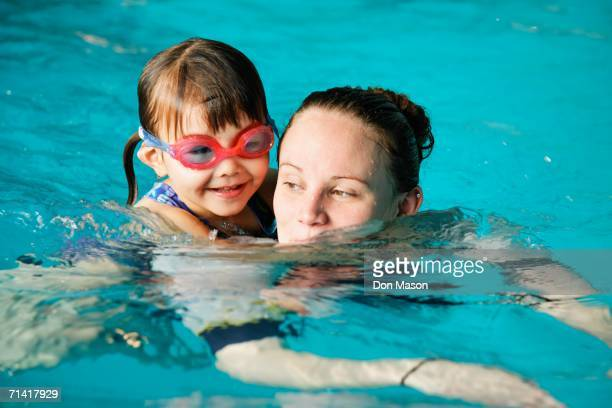 Mother and young daughter swimming