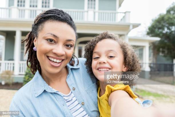 mother and young daughter take selfie in front yard - camera point of view stock photos and pictures