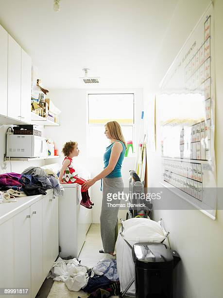 Mother and young daughter talking in laundry room