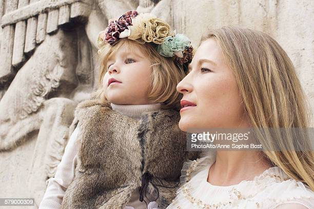 mother and young daughter together outdoors, looking away attentively - anne sophie mutter stock-fotos und bilder