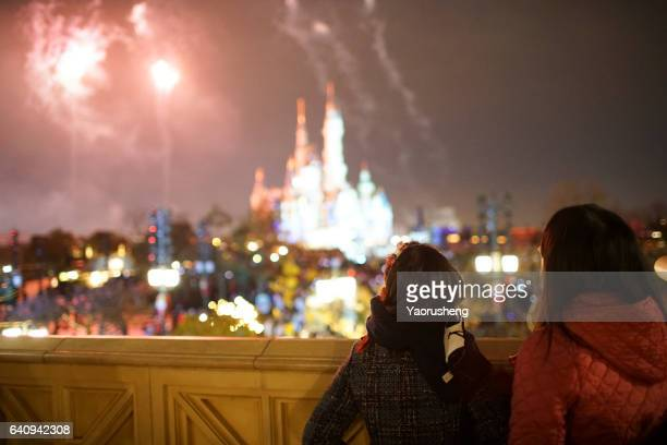 mother and young daugter looking at the firework in holiday