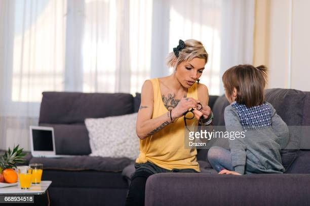 Mother and young daugther playing with disguise mask at home and having fun