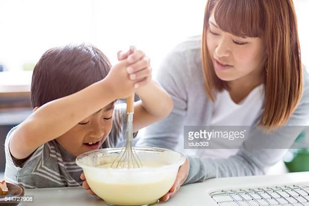 若い母と息子のケーキを焼く