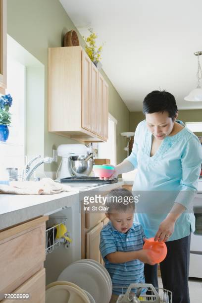 Mother and young son putting dishes in dishwasher