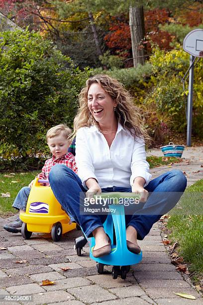 Mother and young son riding on toy cars in garden