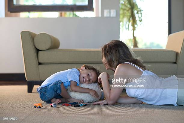 Mother and young son together in living room playing, boy hugging stuffed toy