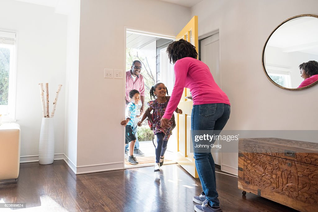 Mother answering the door to her family : Stock Photo