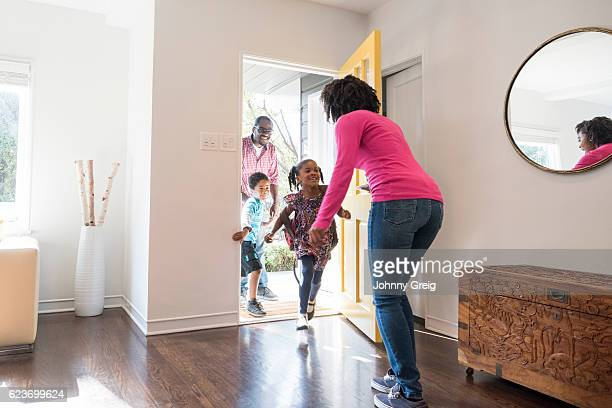mother answering the door to her family - entrando - fotografias e filmes do acervo