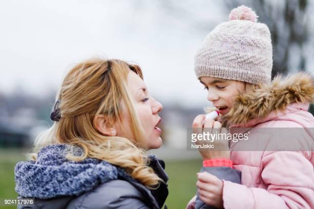 mother applying a lip balm to her child - lip balm stock pictures, royalty-free photos & images