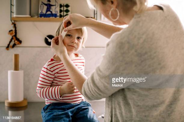 mother applying bandage on daughter's face at home - machucado imagens e fotografias de stock