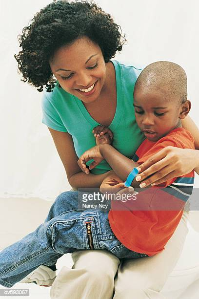 Mother Applying Bandage to Son