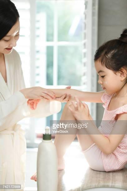 Mother applying body cream on daughter