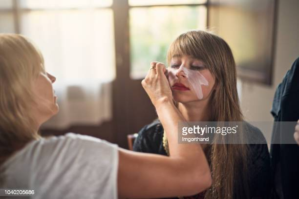 mother applying halloween make up - stage make up stock pictures, royalty-free photos & images