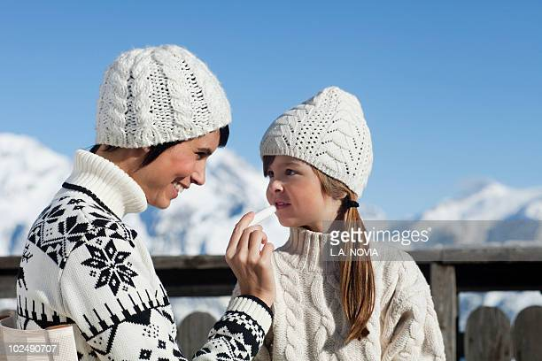 mother applying lip balm to her daughter - lip balm stock pictures, royalty-free photos & images