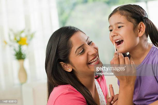 Mother applying lipstick on daughter's (6-7) lips