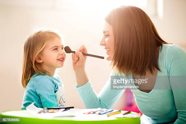 Mother applying make-up to her daughter