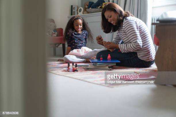 Mother applying nail polish on daughter's toenail